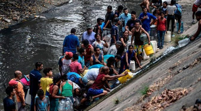 Venezolanos recogen agua en río contaminado tras escasez por apagón (Informador)